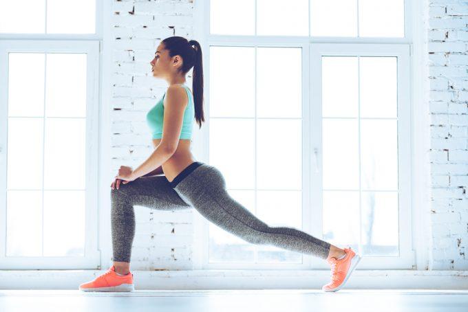 運動前の準備体操におすすめのストレッチ「ランジウォーク」をする女性