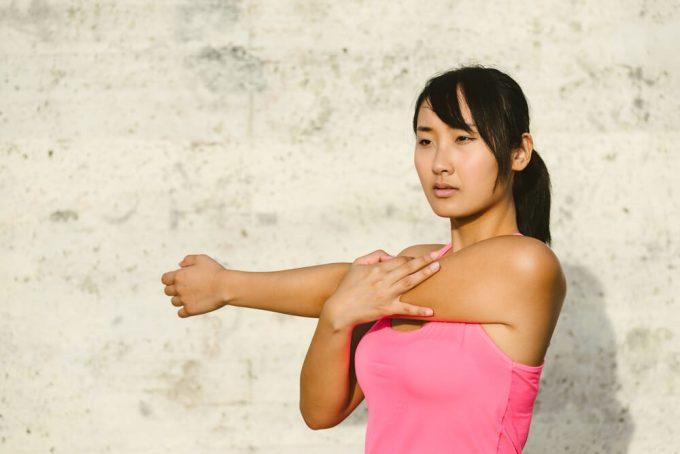 運動後の整理体操におすすめの腕と肩に効くストレッチをする女性