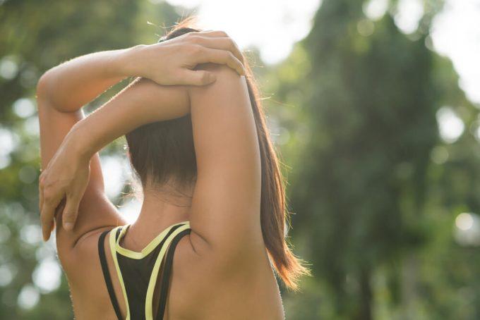 運動後の整理体操におすすめの腕と肩、背中に効くストレッチをする女性