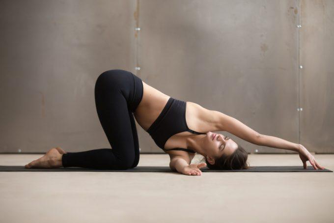 上半身のバランスを整える、肩、背中、脇に効くストレッチをする女性