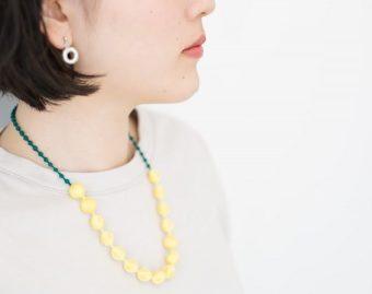 夏の装いを華やかに。光沢のある美しい糸でできた「 000(トリプル・オゥ)」のネックレス