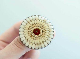 輝く透明感の中にぬくもりを感じる。小さな植物を散りばめた「Cotton cup」のブローチ