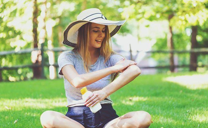 紫外線対策に日焼け止めを塗る女性