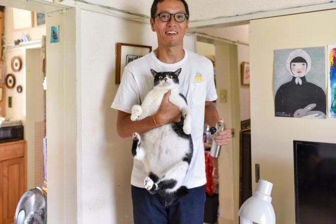 西荻窪にあるショップ&ギャラリー「ウレシカ」の飼い猫びんすけを抱っこする飼い主のダイさん
