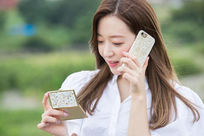 Print creativeのスマホケースをつけた携帯で電話をする女性