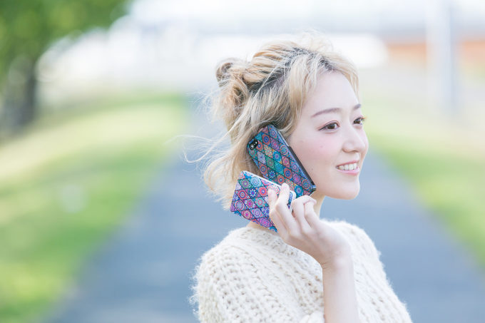 Print creativeのスマホケースをつけた携帯で電話をする女性2