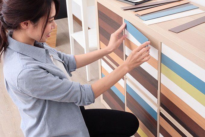 壁や家具に手軽に貼れる天然木の「デコウッドタイル」を貼っているところ