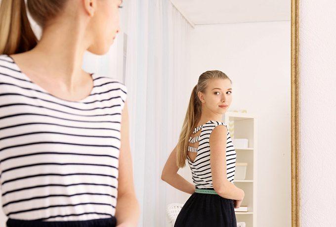 鏡を使って巻き肩のセルフチェックをする女性