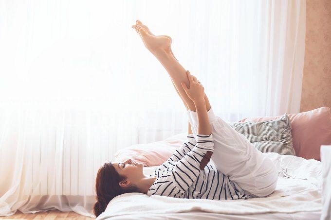 ベッドの上でストレッチをする女性