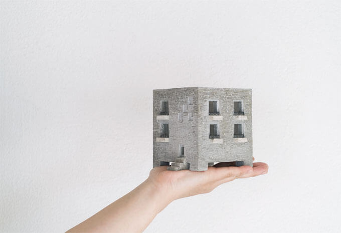 モルタルでできた「Motif」の建物型プランターを手に乗せているところ