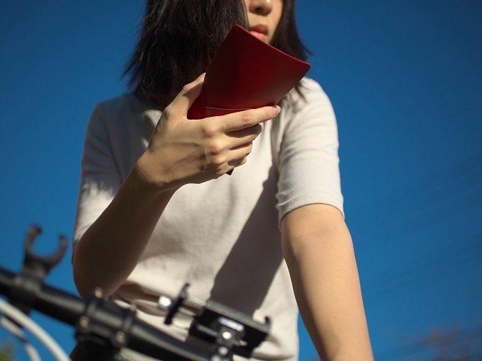 片手で開けられる使い勝手の良い「MYNUS FLIP UP WALLET」の革のミニ財布を持つ女性