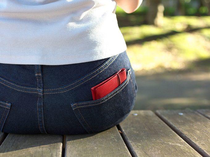 片手で開けられる使い勝手の良い「MYNUS FLIP UP WALLET」の革のミニ財布をポケットに入れた様子