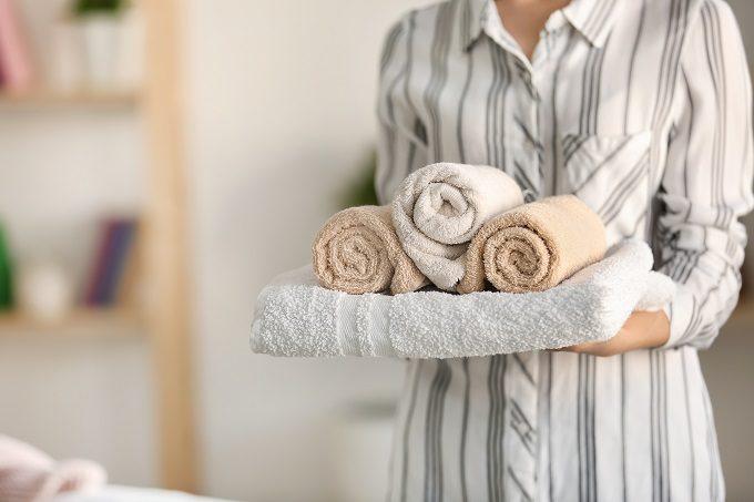 たたまれたタオルを持つ女性