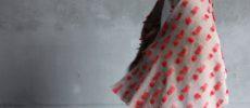 染織作家の高見 由香さんが作る手織りのカシミヤストールを羽織っているところ