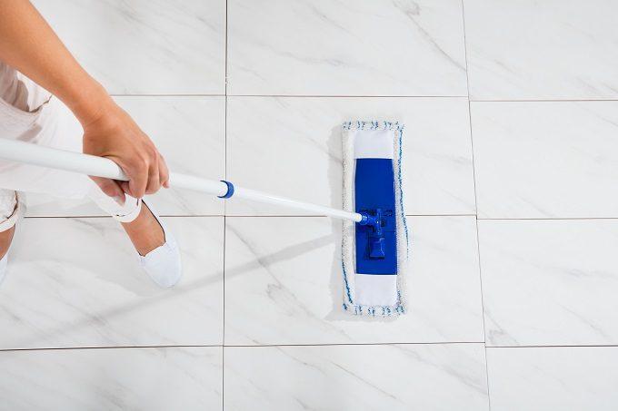 T字型のモップで床掃除をしているところ