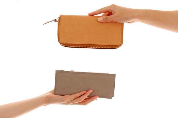 簡単にカバーを付け替えられる「uとto」の革財布を手に持っている様子