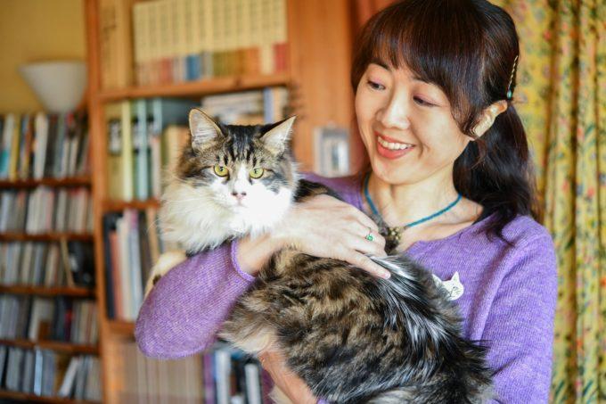 版画家・猫野ぺすかさんが猫を抱く様子