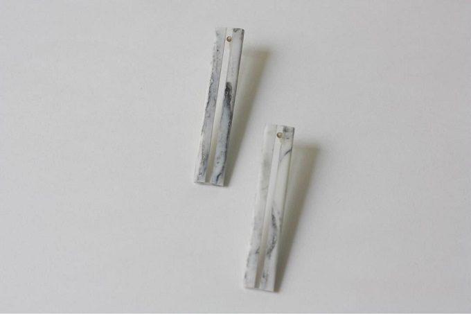 「akari」の細長い白磁の板にアクリルを挟んだピアス