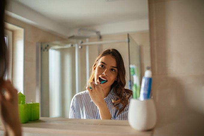 洗面所で歯磨きをする女性