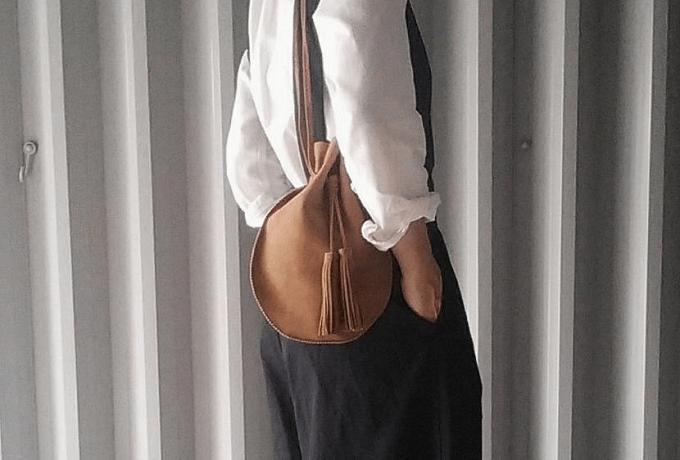 大人女子におすすめの「Chiihao」の革のショルダーバッグを下げているところ