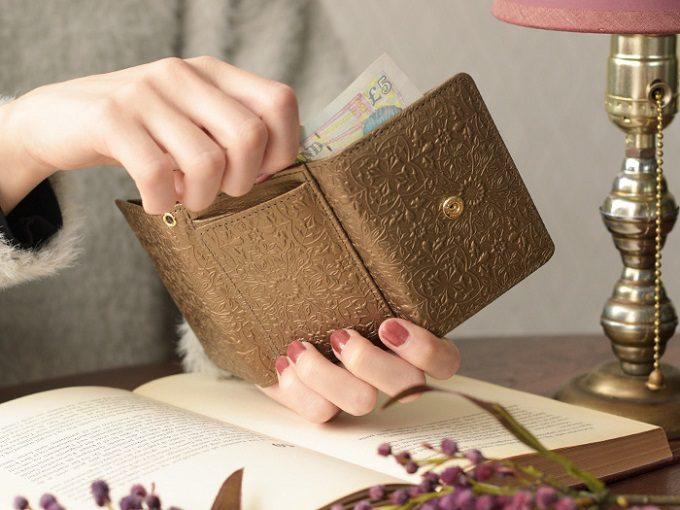 「HIRAMEKI.」の美しい型押しミニ財布からお札を取り出すところ