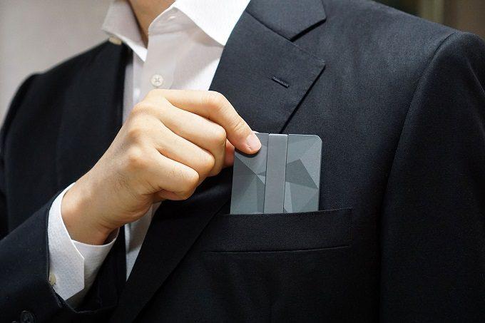 小物や名刺入れにもなるミニ財布「Keri wallet」を胸ポケットから取り出すところ