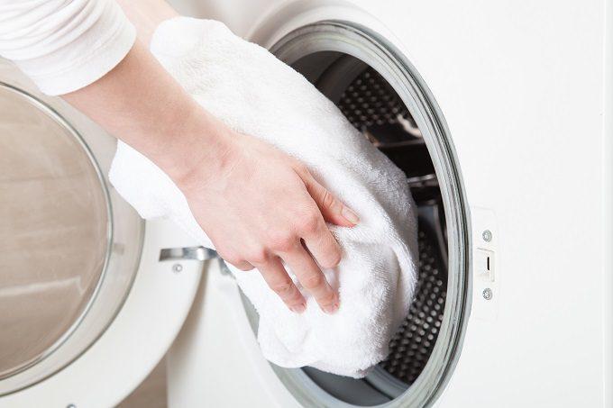 洗濯機にクッションカバーを入れるところ