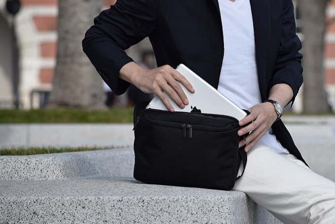 スタイリッシュで機能的なウエストバッグ「SUKIMA bag」にタブレットを入れる様子