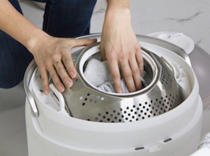 足踏み式のコンパクトな洗濯機「Drumi」を使用しているところ