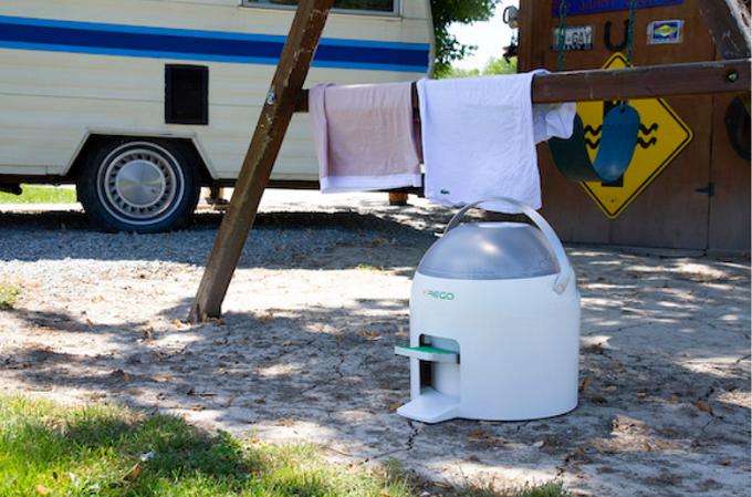屋外に置かれた足踏み式のコンパクトな洗濯機「Drumi」