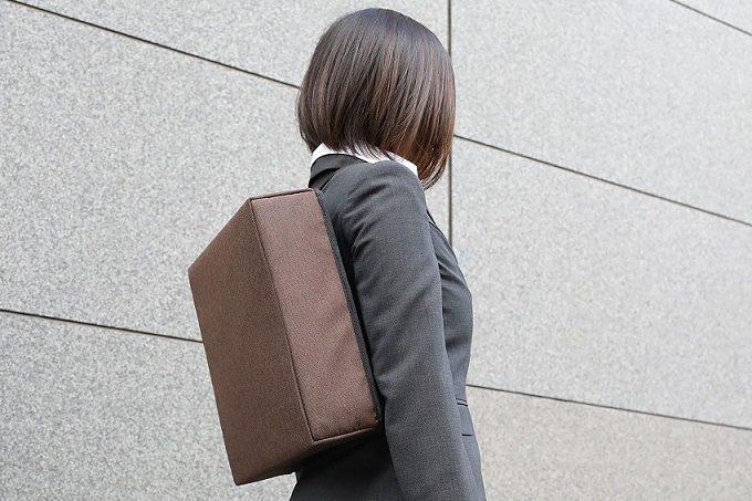 玄関に磁石で設置する防災バッグ「OTE」を背負ったところ