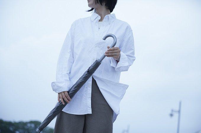 「+TIC LITE(プラスチック ライト)」の「さびない、つよい。長く使える傘」を持つ女性