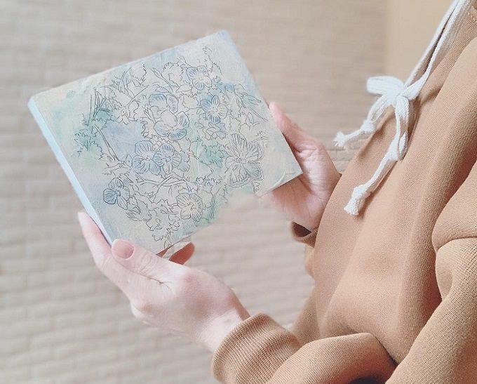 絵画レンタル「Casie」の絵を持った女性の手元