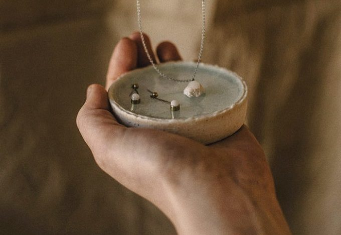 「megumi tsukazaki」の陶器アクセサリーとトレイを手に持ったところ