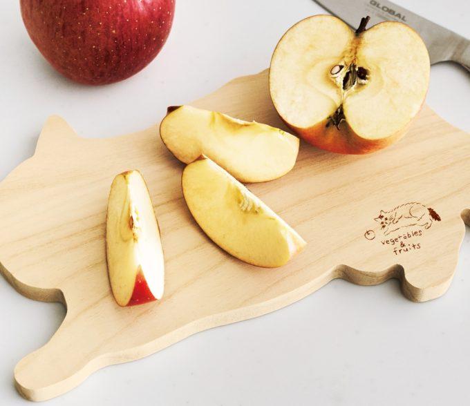 フェリシモ猫部の猫シルエットの両面カッティングボードでりんごを切る様子