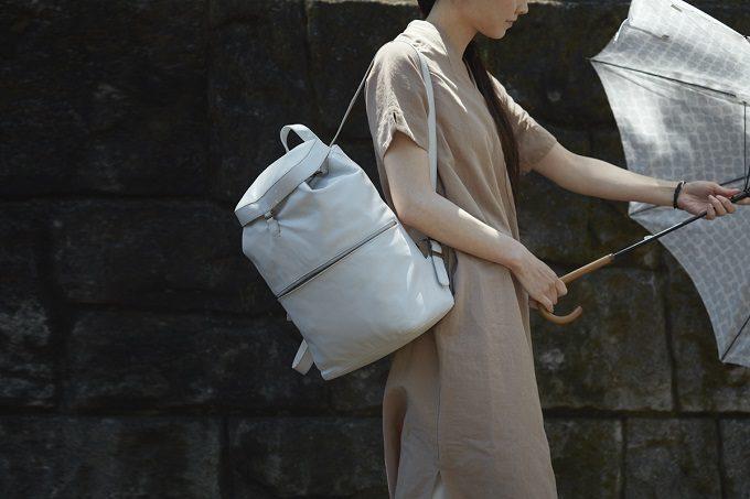 本革を使った「マザーハウス」の撥水バックパックを持つ女性
