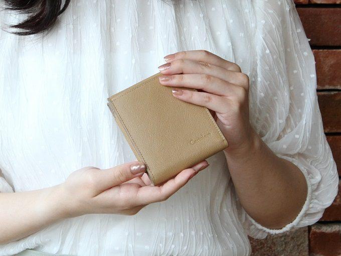 小銭入れ部分がハンモックのように浮き上がって取り出しやすい「ハンモックウォレット」を持った女性