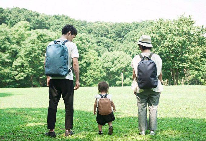 「NIZYU KANO(ニジュウカノウ)」のリュックを背負った3人家族の後ろ姿