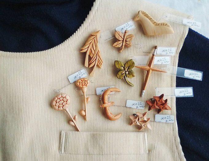木製ブローチのブランド「ao11(アオジュウイチ)」のさまざまな形のブローチを服に合わせたところ
