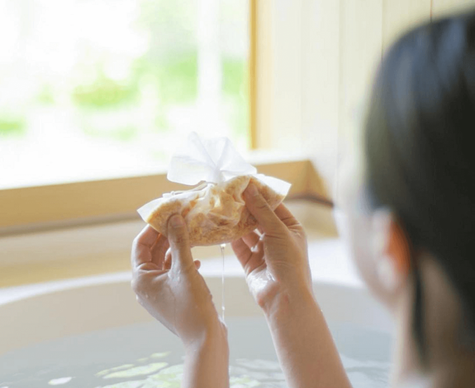 「jiwajiwa」のお風呂のハーブを持って湯船に浸かっているいる女性