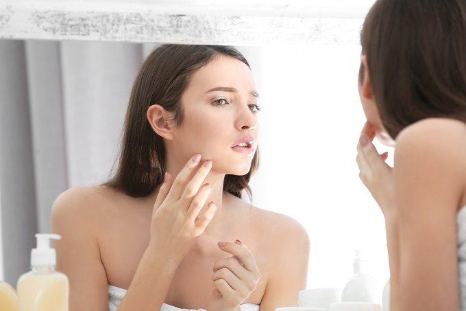 鏡で自分の肌をチェックする女性