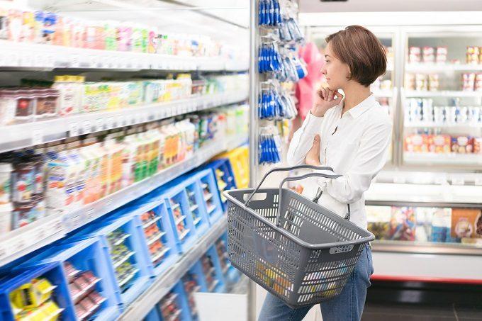お店の棚の前でジュースを選ぶ女性