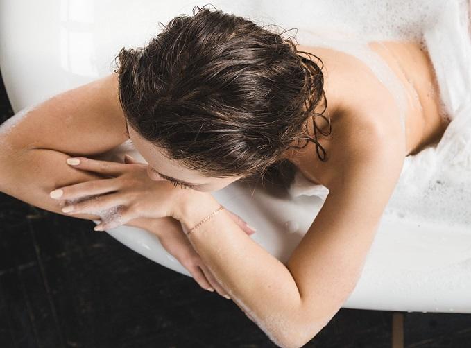 女性が湯船につかっている画像