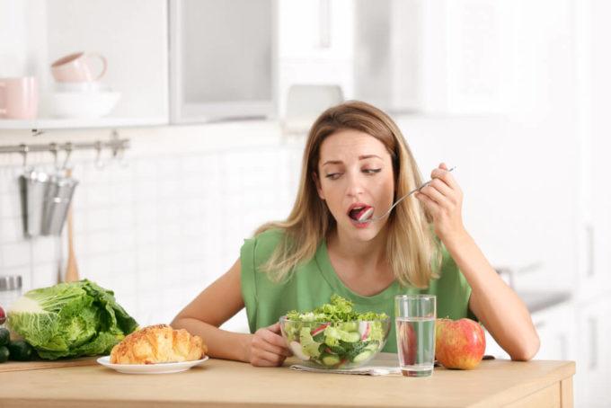 お腹が張ってつらい便秘をすっきり改善するために野菜を食べる女性