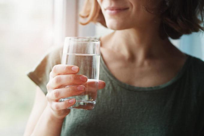 お腹が張ってつらい便秘をすっきり改善するために水分をとる女性