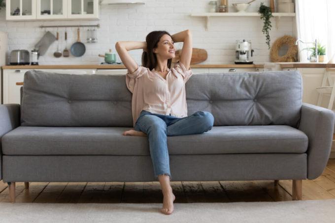 猫背によるぽっこりと出た下腹・お腹が改善し、猫背を治した女性がソファに座る様子