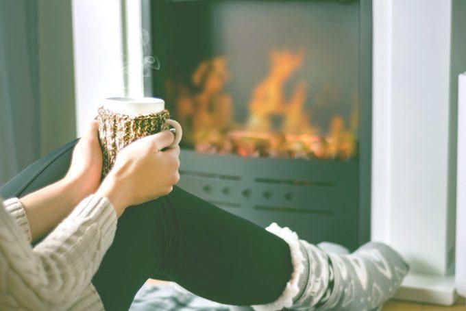 ホットドリンクを手に暖炉前に座る女性の写真