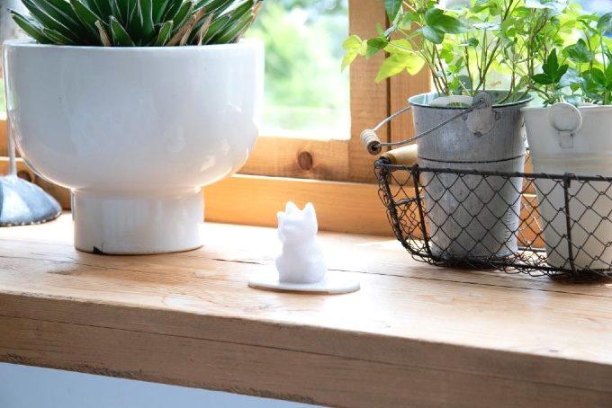 窓際に置かれた招き猫型盛り塩の写真