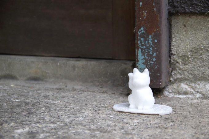 屋外に置かれた招き猫型盛り塩の写真