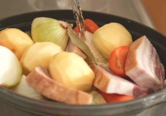 材料を入れた鍋に水を注ぐ写真